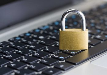 Padlock sitting on laptop keyboard representing the cyber security protections needed to stop cyber criminals from hacking your business.